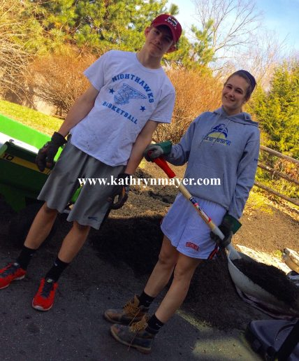 Teenagers mulch yard in spring clean up