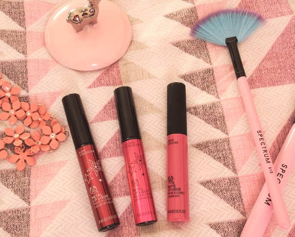 The Body Shop Metal Lip Liquid and Matte Lip Liquid on a pink background with pretty pink props