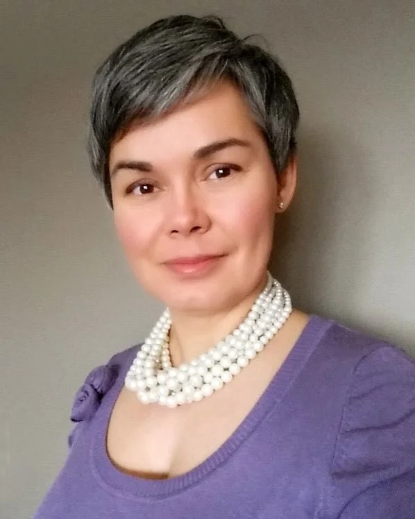 woman pearls purple top gray hair pixie cut