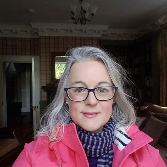 image of pretty woman pink jacket gray hair glasses