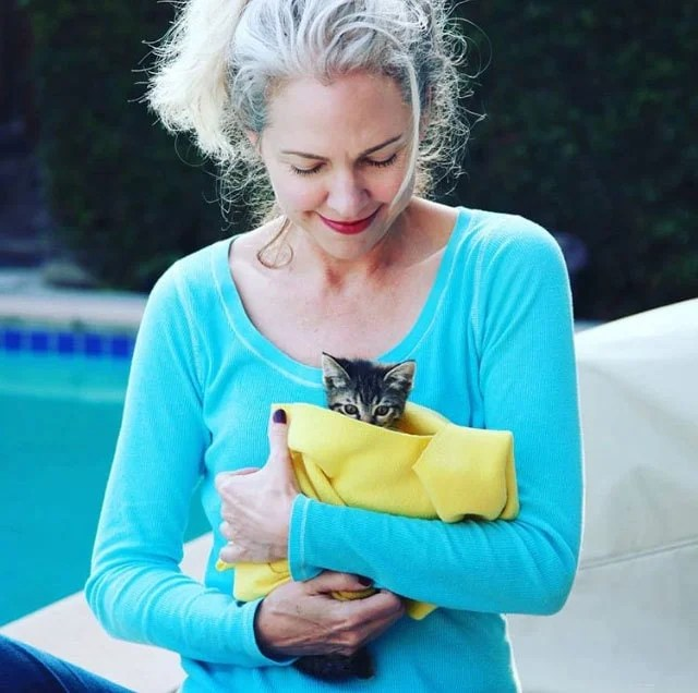 image of pretty woman gray hair blue shirt holding kitten