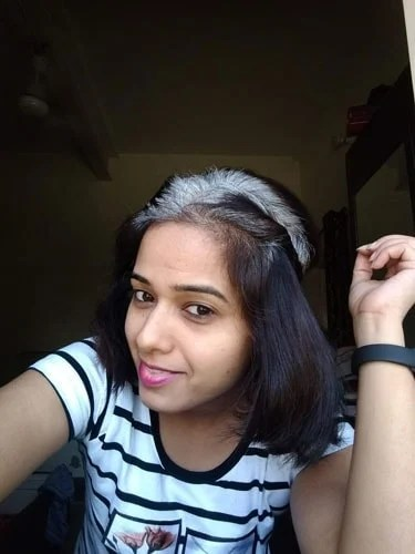 image of young Indian woman white roots black dyed hair