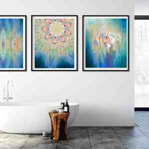 Three blue and yellow paintings hanging on a white a bathroom wall