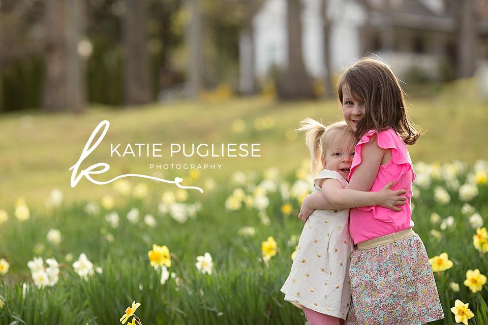 Sisters hugging in flower field