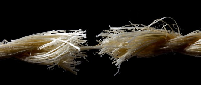 White rope on a black background, about to split apart