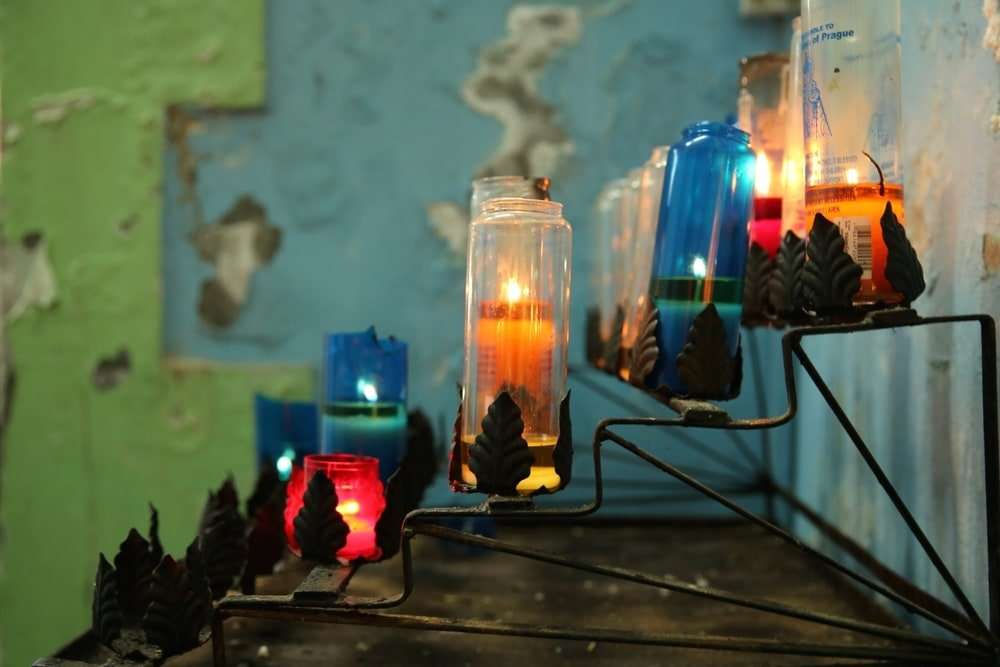 Photograph of multicolored religious candles in glass holders sitting in a multi-tiered metal rack.