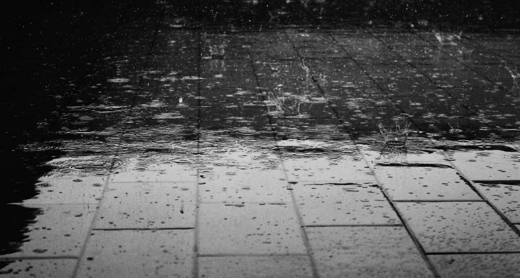 Alt Text: Monochrome photograph of a rain shower on a brick walkway. Image via Pixabay.