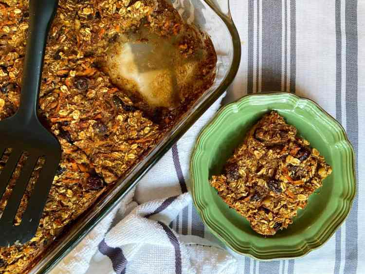 baking dish with carrot cake oatmeal bars in it with one bar on a green plate.