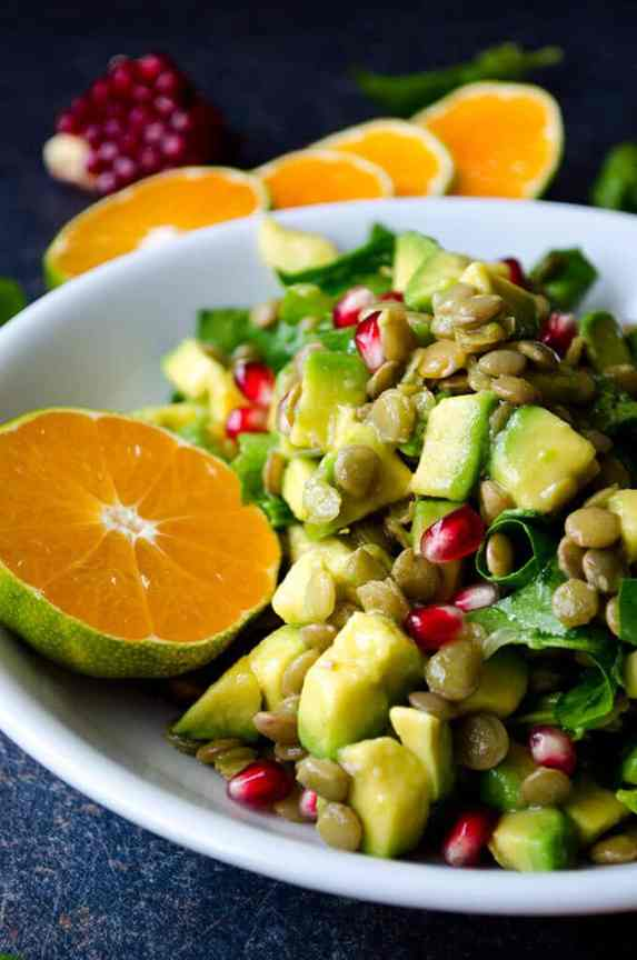 close up image of a salad in a shallow white bowl made of avocado, spinach, lentils, and pomegranate seeds, with a halved orange to garnish