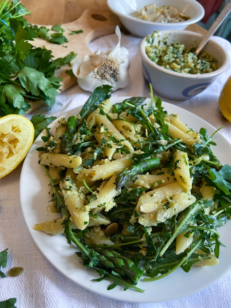 white plate with creamy pasta coated in lemon artichoke pesto, with bright green asparagus spears, and arugula, with lemon, garlic, parsley, and a bowl of pesto in the background.