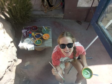 Image of a young seated caucasian woman, wearing large black sunglasses and holding a large container of green paint and paintbrush. more paints are in the background.