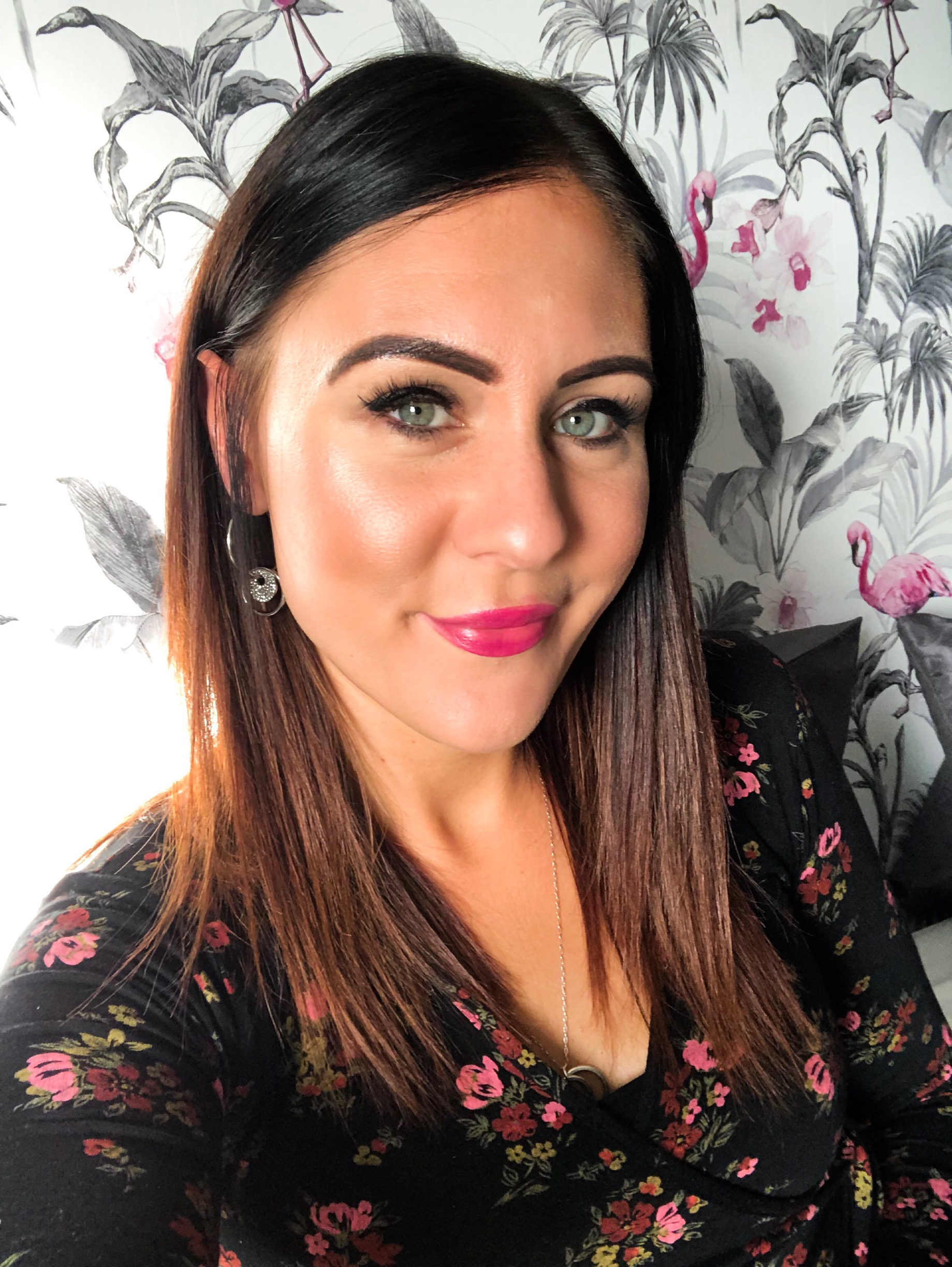 a close up of me with my brown hair down. I am wearing full make up and pink lipstick and have a flowery black top on. I am standing in front of grey wallpaper with flamingos on.