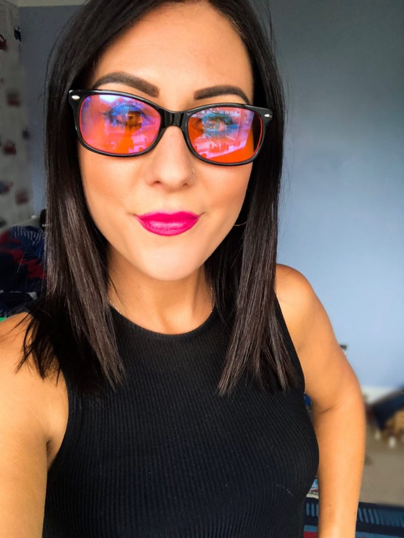 A close up of me with a black top on and my dark hair down. I have orange tinted glasses on and bright pink lipstick.