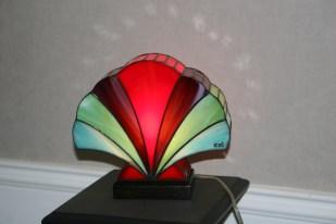 Lampe Art Déco en vitrail Tiffany Coquillage. Verres opalescents rouge, parme, vert anis et bleu cobalt, profonds et lumineux. Socle en noyer massif teinté noir Napoléon. Largeur 25,5 cm, Epaisseur 9 cm, Hauteur 22,5 cm