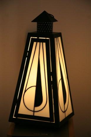 Lampe structure fer noir ornée de 4 panneaux de vitrail Tiffany. Verre américain blanc opalescent et noir. Petite porte pour changer l'ampoule E14 (fournie). Pièce unique et signée. Largeur 18 cm Profondeur 18 cm Hauteur 39 cm