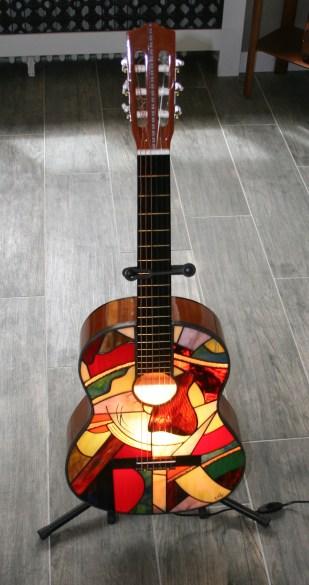 """Nouvel exercice de style autour de l'instrument de musique (4ème éditon). Une guitare d'apprentissage qui a rempli son office et entame une seconde vie. Elle peut trôner avec fierté dans votre salon !!! Chaque modèle est original et unique de par les couleurs et le dessin du panneau de vitrail toujours différent, mais aussi le caisson qui pour ce modèle est couleur noyer roux. Pièce d'exception : extrême originalité, design, élégance mais aussi """"fun"""" pour cette guitare électrifiée pouvant être posée au sol, sur un meuble ou suspendue au mur. Caisson d'une guitare véritable en bois roux dont le panneau avant a été remplacé par un panneau de vitrail constitué de verres opalescents vous garantissant un éclairage d'ambiance doux mais très lumineux. Les verres sont multicolores : bleus ciel, bleu pétrole, bleu cobalt..., gris, différents rouges très lumineux et vifs, différents verts, violets, orange, jaunes, translucides.... choisis pour leur particularité de structure. Quelques-uns d'entre eux étant peints à la grisaille (peinture pour verre cuite à 600 degrés) pour évoquer des ondes. Le tout étant extrèmement lumineux : la photo ne rend pas hommage à cette particularité (difficile de photographier la lumière....). Si vous êtes nostalgique de vos jeunes années d'apprentissage et détenteur d'un instrument que vous souhaitez voir briller une nouvelle fois.....contactez-moi, j'ai certainement une solution à vous proposer. L'ampoule E14 fournie de 40 W peut être changée au moyen d'un système très simple (mode d'emploi fourni) permettant l'accés à l'ampoule."""