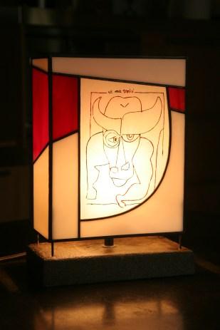 """Lampe Tiffany reproduisant le dessin """"et me voici"""" de Claude Nougaro montée sur socle béton. Avec l'aimable autorisation de Mme Hélène Nougaro"""