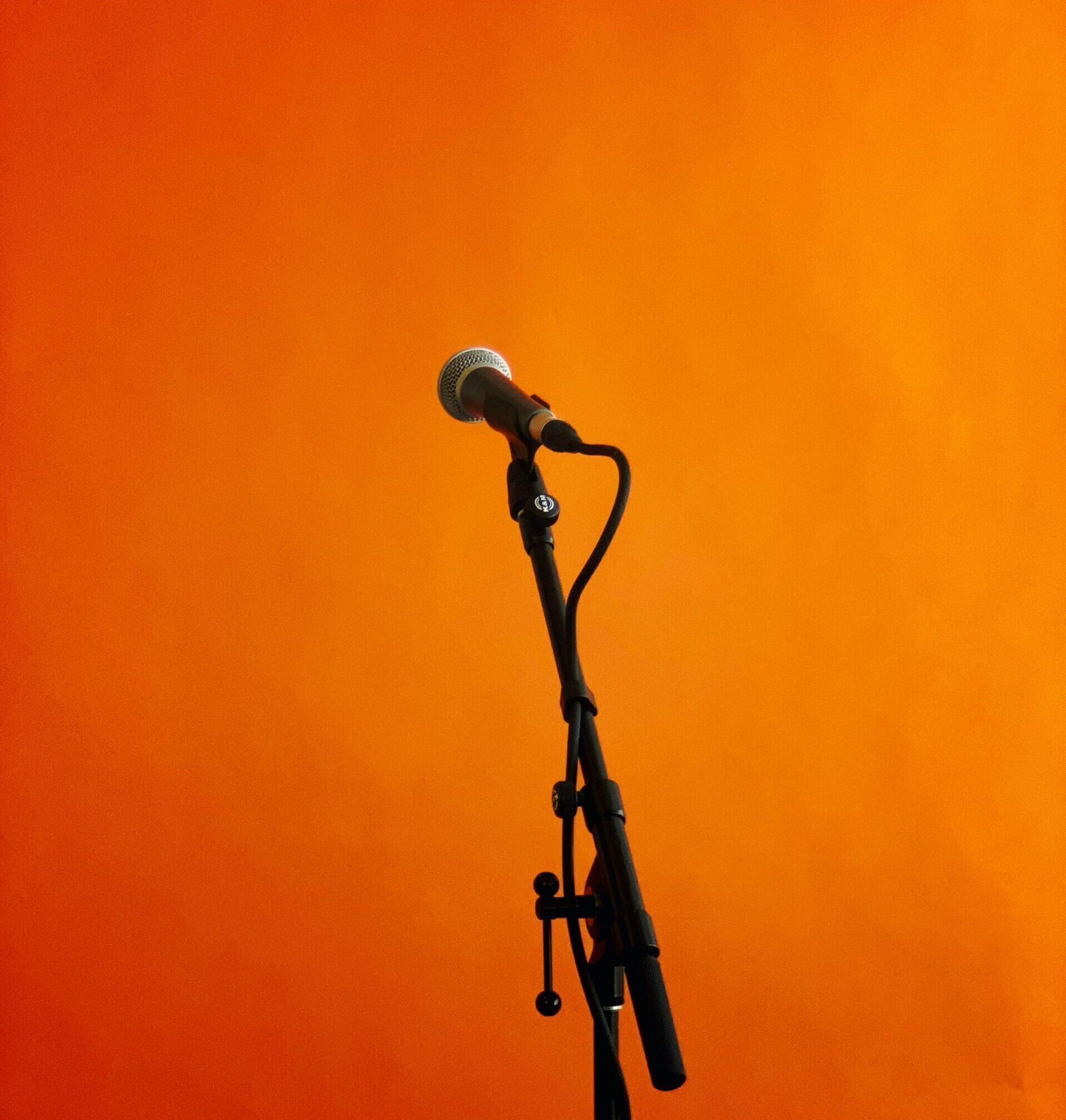 Black microphone and stand on orange background