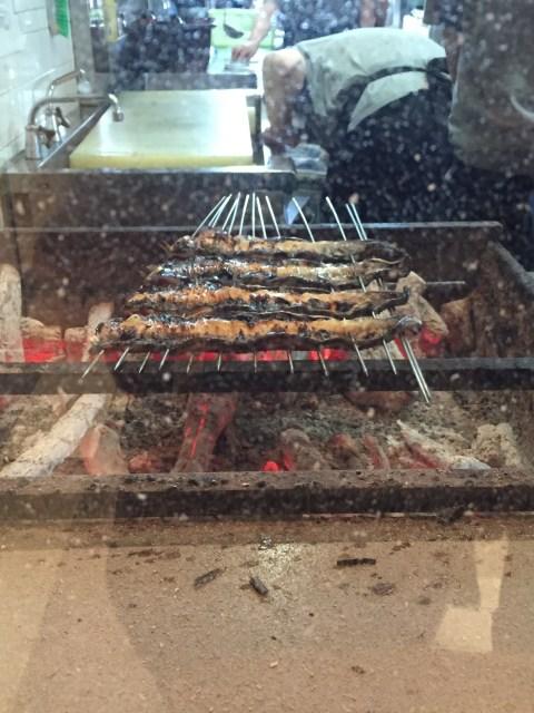 Der Aal wird vor dem Grillen aufgespießt. Die länglichen Spieße verhindern, dass der Aal sich beim Grillen zusammenrollt und erleichtert das Wenden.