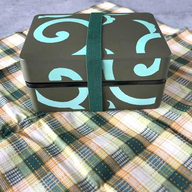 Furoshiki - Anleitung zum Einpacken von Bentoboxen in Tücher: die Bentobox schräg in die Mitte stellen.