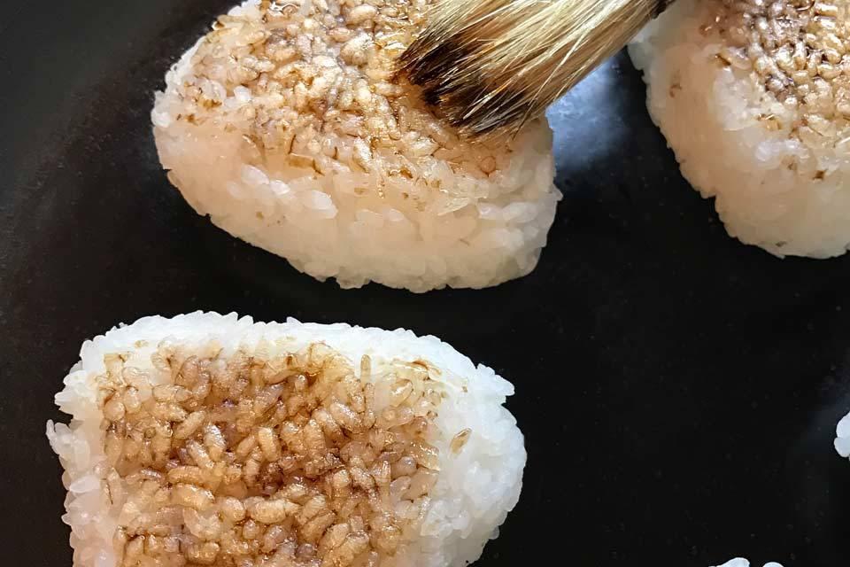 Die dreieckigen Reisbällchen in der Pfanne sanft anbraten und mit Sojasauce bestreichen.