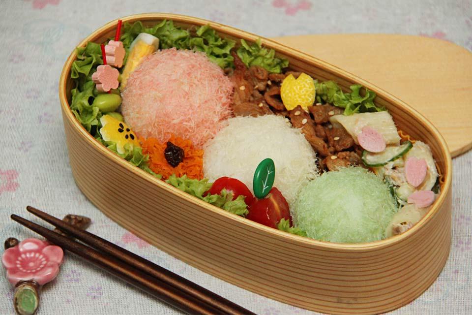 Im Sakura-Bento sind ausserdem krauser Salat, kleine Edamame Spieße, Ei, japanischer Karottensalat, Tomaten, Buta no shōgayaki, Zitrone und ein japanischer Nudelsalat enthalten.