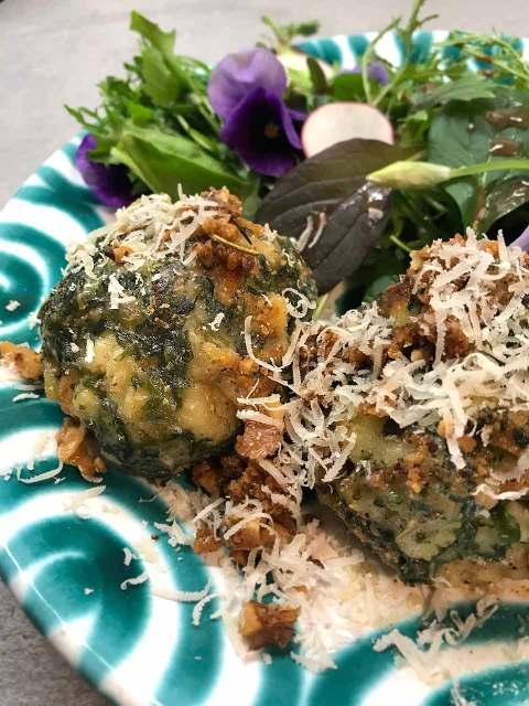 Die gebratenen Bärlauch-Semmelknödel mit einem Miso-Wildkräutersalat und essbaren Blüten.