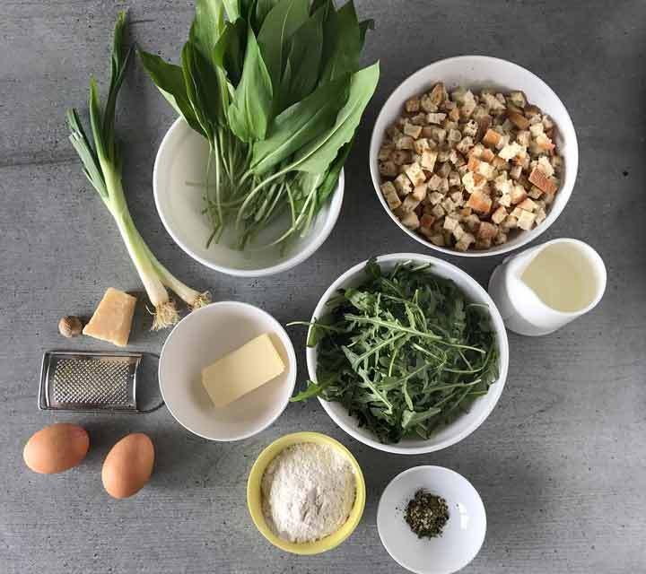 Die Zutaten für die Bärlauch-Ruccola-Semmelknödel: Bärlauch, Ruccola, geschnittene Semmelwürfel, Butter, Mehl, Stärke, Kräuter, Milch und Parmesan.