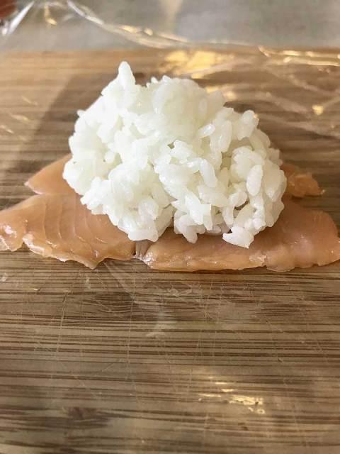Der Sushi-Reis wird auf den Belag gelegt. Der Lachs wurde dazu in Scheiben geschnitten und die Stücke nebeneinander gelegt.