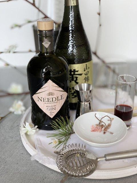 Die Zutaten für den Needle Gin Sakura Martini: Needle Gin, Sake, Kirschsirup und salzig eingelegte Kirschblüten.