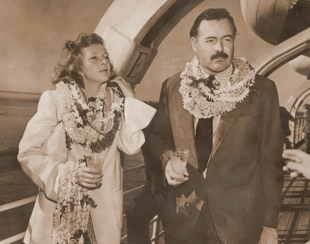 "In this photo from 1941, author Ernest Hemingway (1899 - 1961) and journalist Martha Gellhorn (1908 - 1998), stand on deck aboard a ship, wearing multiple leis and holding cocktails. On Thursday, February 11, author and cocktail historian Philip Greene will present ""Hemingway's Favorite Drinks: His Days in the Gulf Stream,"" at the Custom House Museum as part of the Key West Art & Historical Society Distinguished Speaker Series."