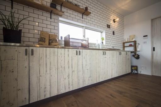 シャビー感のある古材収納 煩雑になりがちなキッチンには収納をふんだんに  収納扉の壁面は古材ペンキ仕上げ。右手奥には広々としたパントリーを設置