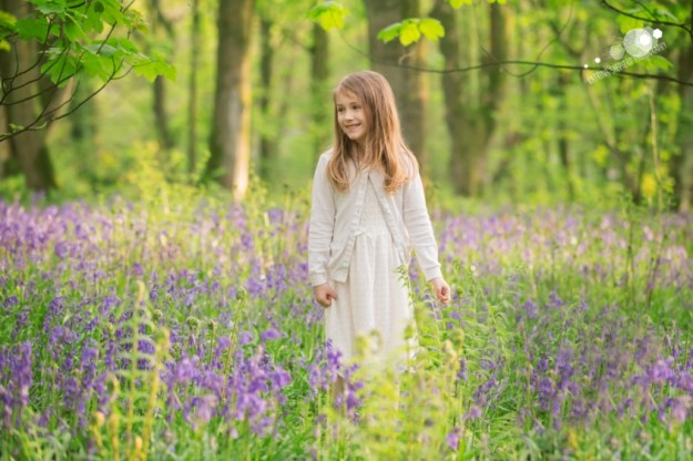 A girl stands amongst the bluebells looking out to the left - Spring Wood near Whalley