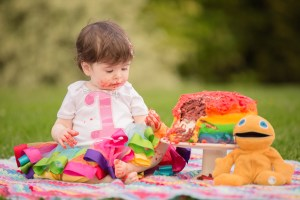 Clitheroe Ribble Valley - Cake smash - cake covered baby sat on a blanket next to a rainbow cake and Zippy stuffed toy