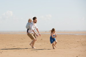 Lytham St Anns Lancashire - A dad carrying a toddler on his back in a wrap chases his daughter across a beach