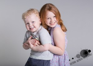 Happy Daze, Darwen - Photo of a sister and brother hugging and looking at the camera