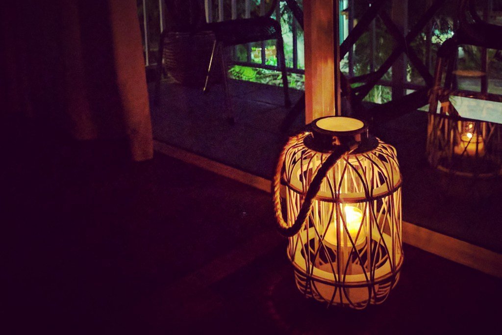 Candle lantern by a glass door