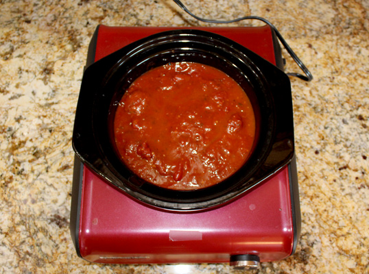 add the meatballs to the slow cooker and cover with sauce