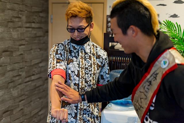 ヒロさんの腕を触るコム