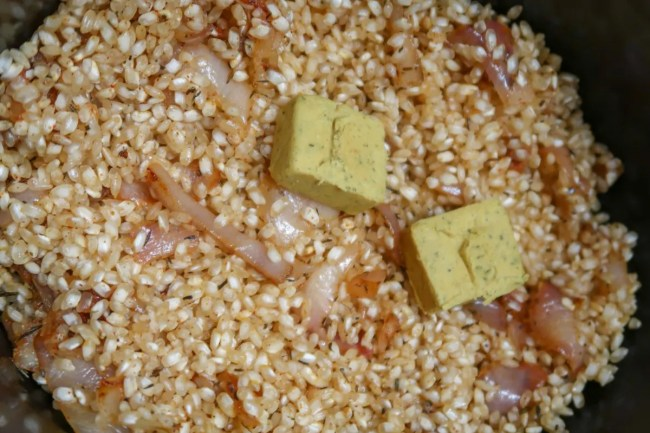 Adding stock cubes to the Slow cooker chicken and prawn paella