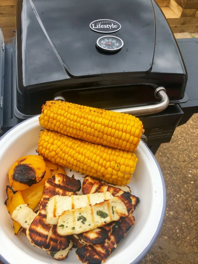 A black 2 burner gas barbecue from Wayfair and a plate of cooked food including corn, halloumi and yellow pepper