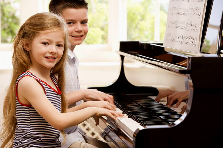 Young girl and boy taking piano lessons at The Conservatory of Music at North Katy