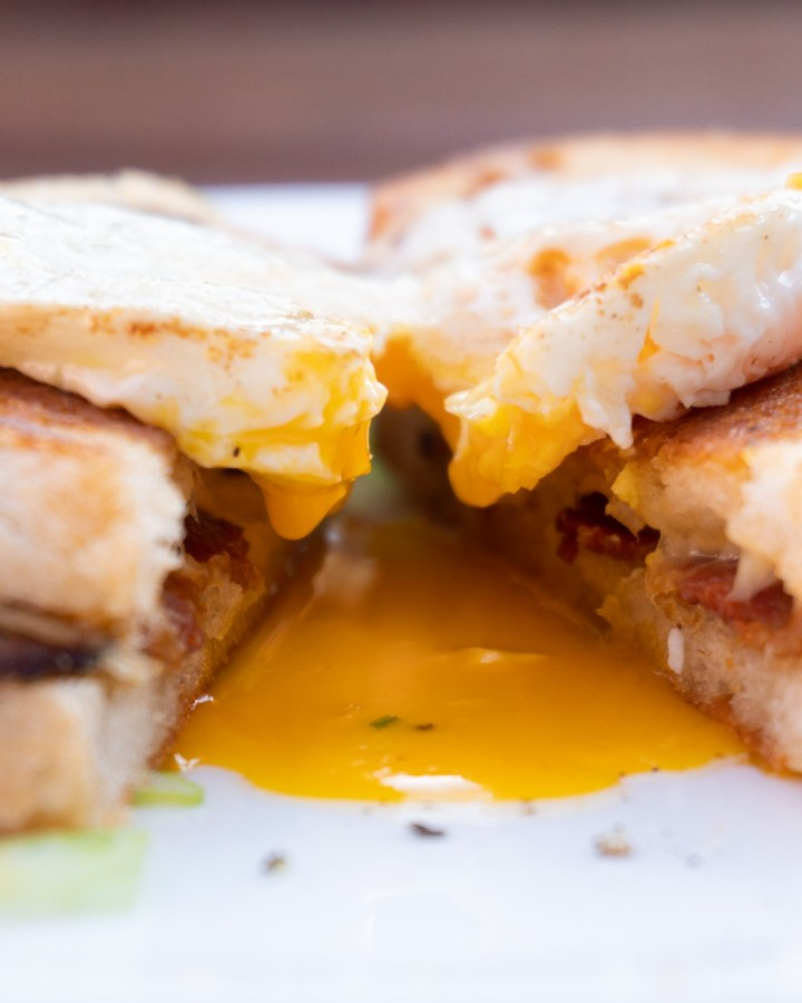 closeup of grilled cheese sandwich with bacon and egg