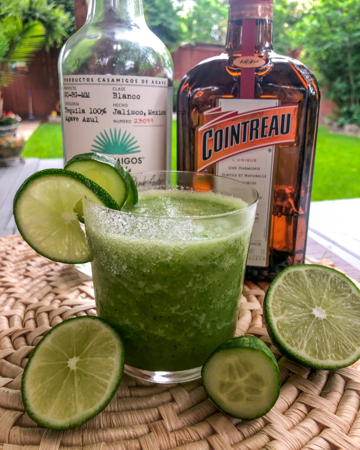 frozen cucumber jalapeno margarita in a glass with ingredients around it