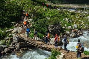 Hampta Pass TTH Trekkers crossing bridge on river