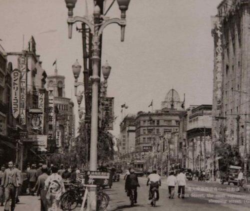 【25】戦争介入で軍隊が行進した銀座。日本が戦争へ介入するに伴って銀座もその影響を受けるようになる。戦局の悪化に伴い1940年(昭和15年)に贅沢品の製造販売禁止令(七・七禁令)や電力制限による広告灯・ネオンサインの消滅、1941年(昭和16年)洋風の店名が禁止され、現在も残る文壇バー「ルパン」(菊池寛、里見弴、泉鏡花、永井荷風、川端康成、久米正雄、林芙美子、太宰治が通った)は、「麺包亭」と名乗って営業したという。 1944年(昭和19年)戦局が苛烈を極め、劇場・料理店・待合芸妓屋・バーが閉鎖され、銀座は大打撃を受けた。その一方、軍隊の行進や、贅沢を諫める運動も街頭で行われた。街灯や都電のレールが取り外され軍事物資に提供され、食糧不足から畑を耕す人も現れた。【25】1940年(昭和15年)頃・(大東京)帝都随一の商店街 銀座通