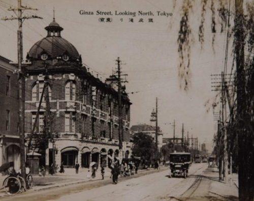 【4】文化人が集うカフェー全盛。1873年(明治6年)、世界一の煉瓦街が銀座に出現。現在の5丁目「メルサ」の場所にあったドームが美しい煉瓦建築。「芝浦モートルス」という袖看板が見える。よく公候伯子男爵の馬車が横付けされ、「田屋」というゴルフ洋品店が入ったという。関東大震災の翌1924年(大正13年)にはカフェー・ライオンの斜向かいの焼けビルを修復し「カフェー・タイガー」が開業した。美人女給がいることで評判となり、永井荷風、菊池寛、中村武羅夫、三上於菟吉らの作家がタイガーをひいきにした。広津和郎の小説『女給』で話題になった菊池寛のカフェー通いはこの店が舞台であった。銀座はカフェー全盛時代。1915年(大正4年)冬には、天皇即位を祝したイルミネーションが外観に灯された。【4】1915年(大正4年)頃・銀座通り(東京)