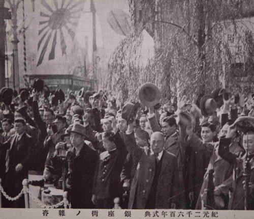 【29】享楽から戦争の時代へ。日中戦争(支那事変)の長期化、物資統制による国民生活の窮乏や疲弊感を、様々な祭りや行事への参加で晴らそうと、1940年(昭和15年)「紀元二千六百年式典」が盛大に開催された。神武天皇の即位から2600年目を祝い、「神国日本」の国体観念を徹底させようという動きが時節により強められた。内閣主催の行事が繰り広げられて国民の祝賀ムードは最高潮に達し、奉祝曲も作曲された。しかし参加者への接待も簡素化され、終了後に貼られた大政翼賛会のポスター「祝ひ終つた。さあ働かう!」の標語の如く、再び引き締めに転じ、その後戦時下の国民生活は厳しさを増していくことになる。銀座では、贅沢は敵だ、パーマネントはやめましょうと呼びかけられ、1944年(昭和19年)街灯や都電のレールが取り外されて軍事物資に提供され、歌舞伎座も休場を命じられ、華やかなネオンも消えた。昭和通りは芋畑に変わった。1945年(昭和20年)1月、泰明小学校にも撃弾が落とされ、その後、度重なる空襲を受け全域が焼き尽くされた。【29】1940年(昭和15年)・東京 紀元2600年式典 銀座街