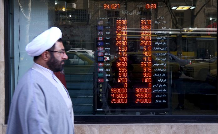 FILE PHOTO: A cleric walks past a currency exchange shop in Tehran's business district, Iran. REUTERS/Raheb Homavandi/TIMAATTENTION EDITORS - THIS IMAGE WAS PROVIDED BY A THIRD PARTY. FOR EDITORIAL USE ONLY.
