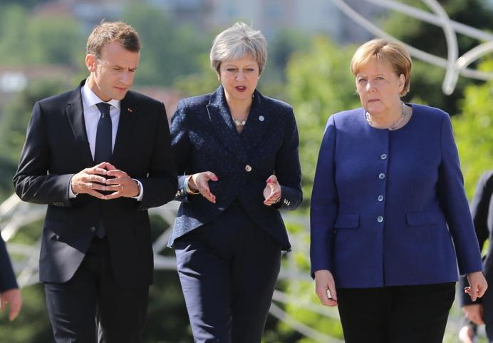 FILE PHOTO: French President Emmanuel Macron, British Prime Minister Theresa May and German Chancellor Angela Merkel walk during the EU-Western Balkans Summit in Sofia, Bulgaria, May 17, 2018. REUTERS/Stoyan Nenov